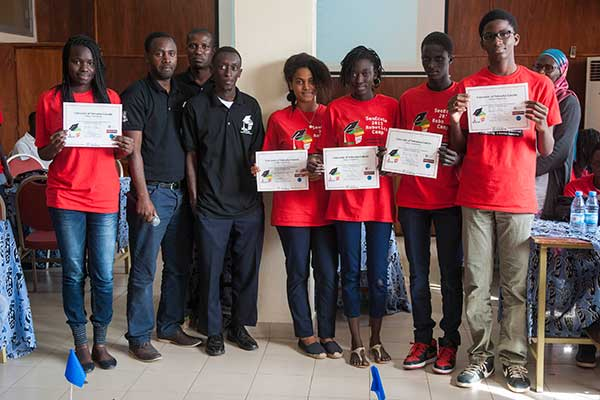 Sidy Ndao, assistant professor of mechanical and materials engineering, hands out certificates to the students after they completed the SenEcole robotics camp in Dakar, Senegal this past March.