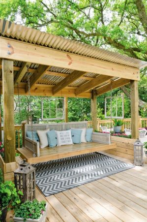 Love this Porch Swing Bed with the metal roof above it_ flower boxes along the side_ and hanging woo
