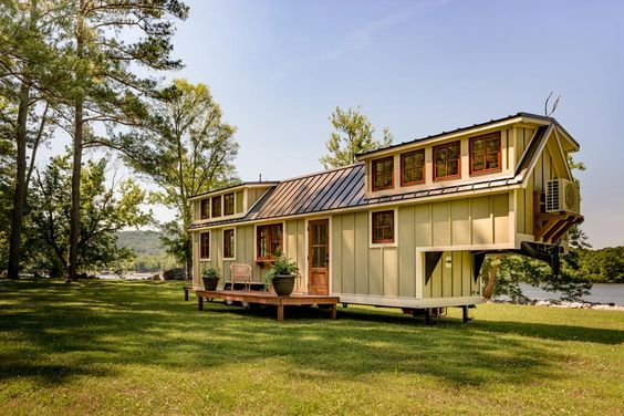 This gooseneck tiny house includes 23 wood clad windows_ two exterior doors_ a folding rear porch_ a.