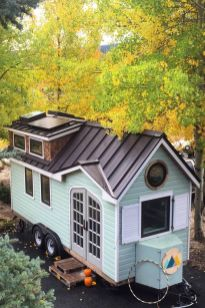 This tiny house has beautiful French doors_ a large living room with a wood burning stove_ and a kit. (1)