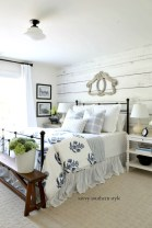 iron-bed-blue-white-bedding-pillows-bench-nightstands-planked-wall