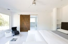 Bedroom-with-sliding-barn-door-and-white-walls-paint