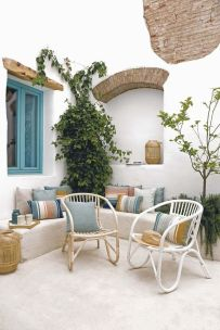 a-Mediterranean-beach-patio-with-wicker-furniture-bright-pillows-potted-plant-and-woven-candle-lanterns
