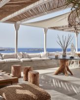 a-beach-patio-with-a-concrete-bench-neutral-upholstery-wooden-and-woven-furniture-and-accessoeies-and-a-beautiful-sea-view