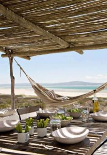 a-beach-patio-with-a-roof-wooden-and-wicker-furniture-a-hammock-some-tableware-and-a-gorgeous-sea-view
