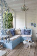 a-beachy-porch-with-vintage-blue-and-white-furniture-printed-blue-pillows-a-whimsical-chandelier-and-macrame-is-very-welcoming