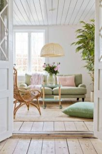 a-beautiful-pastel-living-room-with-a-light-green-sofa-and-a-pillow-a-pink-pillow-and-a-blanket-a-wicker-lamp-and-a-rattan-chair