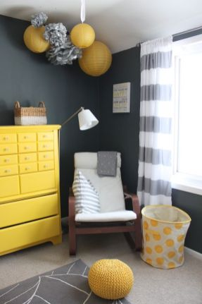 a-black-white-and-yellow-nursery-with-paper-lamps-and-pompoms-a-yellow-dresser-a-rocker-a-basket-and-a-knit-ottoman-plus-striped-curtains