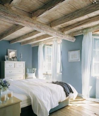 a-blue-bedroom-with-wooden-beams-on-the-ceiling-neutral-furniture-artworks-and-some-blooms