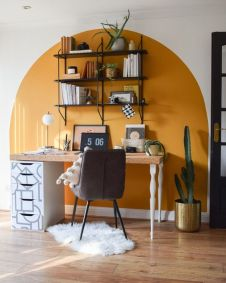 a-boho-working-space-with-a-color-block-yellow-wall-a-desk-with-a-cork-top-a-cofy-chair-an-open-shelving-unit-and-some-cacti