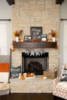 a-bold-Thanksgiving-mantel-with-lots-of-dried-leaves-wheat-pumpkins-of-various-materials-garlands-and-several-signs