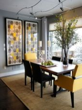 a-bold-modern-dining-room-with-grey-walls-a-panoramic-view-bold-artworks-a-dining-table-black-and-yellow-chairs-and-catchy-lights