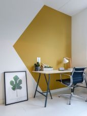 a-bold-modern-working-nook-with-a-mustard-and-white-color-block-wall-a-lightweight-desk-a-black-chair-and-a-greenery-print