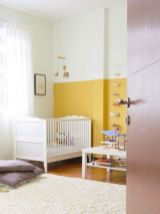 a-bold-nursery-with-a-mustard-and-white-color-block-wall-white-furniture-colorufl-toys-and-lilac-pillows-and-white-textiles
