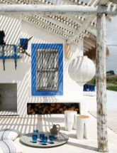 a-bold-white-and-blue-beach-patio-with-framed-shutters-white-furniture-striped-textiles-a-paper-lamp-and-blue-accessories