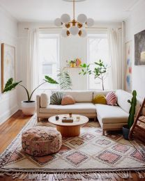 a-bright-and-chic-modern-living-room-with-a-neutral-sofa-a-boho-rug-and-ottoman-pastel-pillows-and-potted-plants