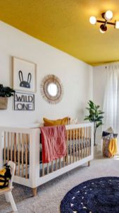 a-bright-and-fun-nursery-with-a-yellow-ceiling-some-yellow-linens-layered-rugs-a-crib-and-a-pretty-gallery-wall-in-boho-style