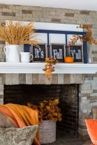 a-bright-and-simple-Thanksgiving-mantel-with-wheat-in-a-jug-chalkboard-signs-window-frames-bold-pumpkins-and-fruits