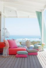 a-bright-beach-deck-with-colorful-furniture-cushions-and-textiles-candle-lanterns-and-turquoise-curtains-and-a-gorgeous-sea-view