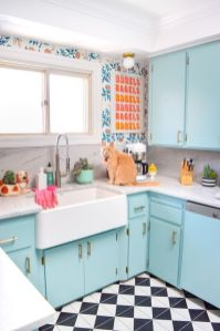a-bright-blue-kitchen-with-printed-wallpaper-a-colorful-artwork-and-a-tiled-floor-is-fun-and-welcoming