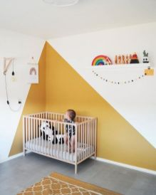 a-bright-modern-nursery-with-yellow-color-blocking-on-the-wall-and-a-yellow-rug-a-neutral-crib-a-shelf-with-toys-and-some-posters