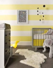 a-bright-nursery-with-a-striped-yellow-and-white-wall-grey-furniture-a-faux-fur-rug-some-toys-and-a-poster