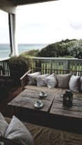 a-casual-seaside-patio-with-simple-wooden-furniture-neutral-printed-pillows-candle-lanterns-and-potted-grasses