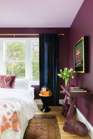 a-catchy-purple-bedroom-with-bold-walls-a-bed-a-console-table-on-animal-like-legs-navy-curtains-and-a-bold-artwork