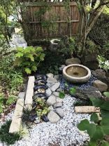 a-chic-Japanese-front-yard-with-pebbles-rocks-a-stone-bowl-with-a-fountain-trees-greenery-and-bamboo