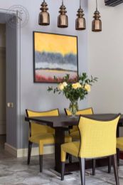 a-chic-and-bright-dining-space-with-a-grey-and-lavender-wall-a-dark-table-bright-yellow-chairs-a-colorful-artwork-and-pendant-lamps