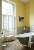 a-chic-bathroom-with-grey-and-yellw-color-block-walls-a-grey-tub-a-wooden-floor-and-shutters-for-privacy
