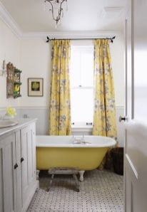 a-chic-vintage-bathroom-with-grey-paneling-a-yellow-bathtub-yellow-floral-curtains-printed-tiles-and-a-crystal-chandelier