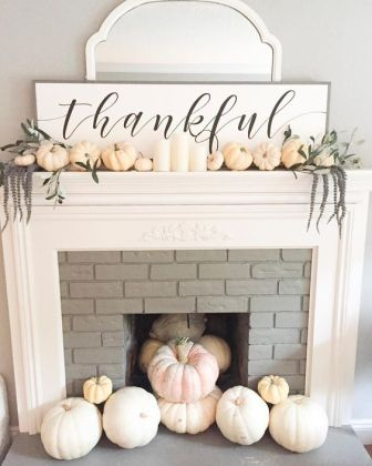 a-chic-white-Thanksgiving-mantel-with-pumpkins-long-flowers-white-candles-a-sign-and-a-mirror-behind-it
