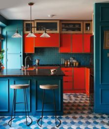 a-colorful-kitchen-with-bright-red-cabinets-navy-cabinets-walls-and-a-backsplasj-plus-a-retro-pendant-lamp-and-a-scallop-tile-floor