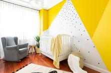 a-colorful-nursery-with-a-yellow-and-polka-dot-accent-wall-a-white-crib-and-a-grey-chair-a-basket-and-potted-plants-looks-cool