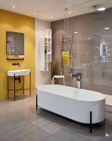 a-contemporary-bathroom-with-a-grey-wall-and-a-yellow-one-white-appliances-a-shower-space-and-a-couple-of-racks-for-storage