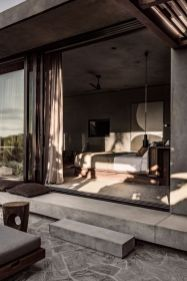 a-contemporary-bedroom-in-earthy-tones-with-statement-art-and-a-sliding-glass-door-that-leads-to-a-terrace-is-a-lovely-room