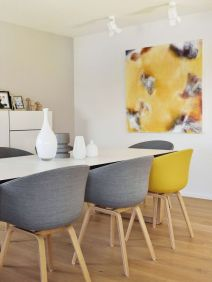 a-contemporary-dining-room-with-neutral-walls-a-storage-unit-a-white-table-grey-and-yellow-chairs-and-a-matching-artwork