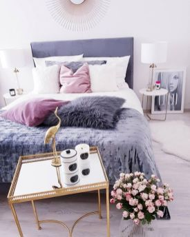 a-contemporary-glam-bedroom-in-white-with-a-purple-bed-pink-and-purple-pillows-round-nightstands-and-table-lamp-plus-a-mirror-table