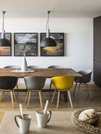 a-contemporary-grey-and-yellow-dining-room-with-a-wooden-table-grey-black-and-yellow-chairs-pendant-lamps-and-a-matching-gallery-wall