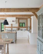 a-contemporary-kitchen-with-white-cabinetry-a-grey-kitchen-island-and-wooden-detailing-plus-wooden-beams-is-very-cozy