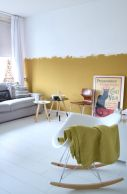a-contemporary-living-room-with-a-mustard-color-block-wall-chic-furniture-round-tables-and-a-rocker-and-a-vintage-poster