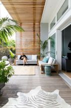 a-contemporary-sea-terrace-with-sofas-with-neutral-upholstery-rugs-pillows-and-potted-plants-is-welcoming