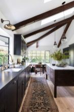 a-contrasting-kitchen-with-dark-cabinets-and-a-stained-kitchen-island-dark-wooden-beams-pendant-lamps-and-lights