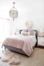 a-cool-girlish-bedroom-with-a-grey-bed-pink-and-neutral-bedding-a-blush-rug-a-beaded-chandelier-and-touches-of-gold