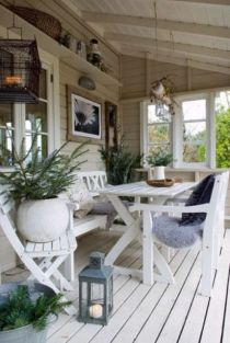 a-covered-beach-patio-with-a-white-deck-and-white-wooden-furniture-potted-plants-candle-lanterns-and-some-vintage-stuff-for-decor