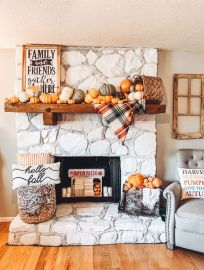 a-cozy-and-chic-Thanksgiving-mantel-with-lots-of-pumpkins-a-basket-a-plaid-blanket-a-sign-and-some-pumpkins-in-a-crate