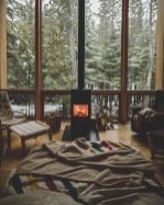 a-cozy-boho-bedroom-with-a-bed-comfy-chairs-and-stools-a-fireplace-in-the-center-and-a-glazed-wall-with-a-forest-view