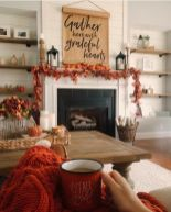 a-cozy-rustic-Thanksgiving-mantel-with-a-bold-leaf-garland-orange-pumpkins-a-paper-hanging-and-candle-lanterns