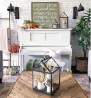 a-fall-or-Thanksgiving-mantel-with-heirloom-pumpkins-paper-leaves-and-blooms-lanterns-with-wheat-and-some-signs